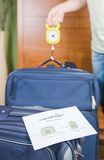 Woman checking luggage weight with a hand balance Royalty Free Stock Photos