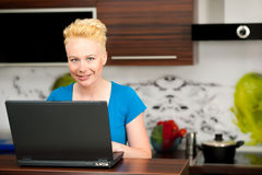 Woman checking mail on laptop in kitchen Stock Photography
