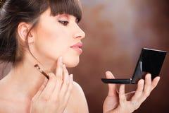 Woman checking makeup. Pretty woman checking face skin looking at mirror Royalty Free Stock Photo