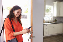 Woman Checking Mobile Phone As She Opens Door Of Apartment Stock Photography