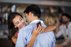 Woman checking mobile phone while embracing man Stock Photography