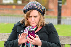 Woman checking mobile phone Stock Images