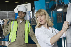 Woman Checking Newspaper By Colleague In Factory Royalty Free Stock Image