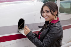 Woman checking oil in airplane Stock Image