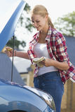 Woman Checking Oil Level In Car Engine Royalty Free Stock Photography
