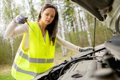 Woman checking oil level Royalty Free Stock Photo