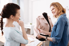 Woman checking out the sleeve of a jacket. Love the quality. Pleasant smiling women touching the sleeve of a jacket as well as showing it to the colleague Royalty Free Stock Images
