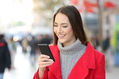 Woman checking phone messages on the street in winter royalty free stock photos