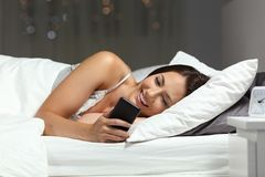 Woman checking phone in the night on the bed stock image