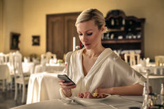 Woman checking phone in a restaurant. Blond young businesswoman checking her phone whilst sitting at a restaurant table with her meal infront Royalty Free Stock Images