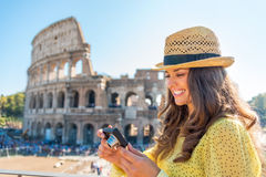 Woman checking photos in front of colosseum Royalty Free Stock Photos