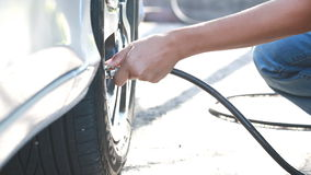 Woman checking pressure and inflating car tire. stock video