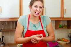 Woman checking pulse on wrist. Mature woman checking pulse on wrist. Stressed female in kitchen Stock Photo