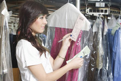 Woman Checking Receipts Of Dry Clean Clothes In Laundry Stock Photo