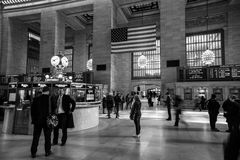 Woman checking the schedule of trains at Grand Central Station. Other people running or just talking. Royalty Free Stock Photos