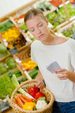 Woman checking shopping list. Woman checking her shopping list Stock Photo