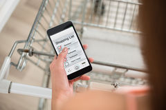 Woman Checking Shopping List On Smartphone In Supermarket. High angle view of woman with pushcart checking shopping list on smartphone in supermarket Stock Images