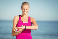 Woman checking time on beach Stock Photography