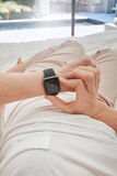 Woman checking time on her smartwatch Stock Photography