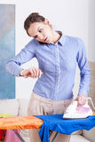 Woman checking time during ironing clothes Royalty Free Stock Photos