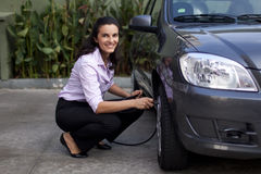 Woman checking tire pressure Royalty Free Stock Photo