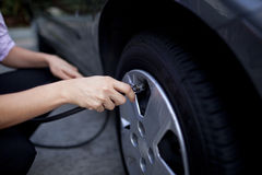 Woman checking tire pressure Stock Photos