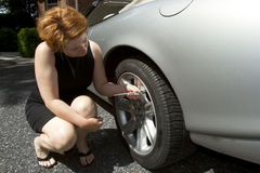 Woman Checking Tire Pressure Royalty Free Stock Photography
