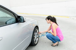 Woman checking tires. Woman pumping air to the tires and cheking pressure before travel Stock Photos