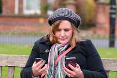Woman checking two mobile phones. Messages Stock Images