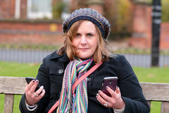 Woman checking two mobile phones. Woman checking messages on two mobile phones Stock Photography
