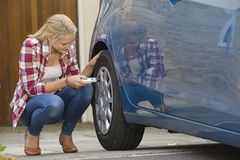 Woman Checking Tyre Pressure On Car Royalty Free Stock Photo