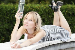 Woman checking water quality. Pretty blonde woman laying on bench in park and looking at bottle closeup shot Royalty Free Stock Photography