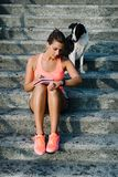 Woman checking workout time and training program. Fitness woman taking workout routine notes and timing training. Female athlete sitting on stairs with her dog royalty free stock images