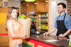 Woman at checkout counter in a grocery store. Cute young brunette ready to pay for her groceries at a checkout counter in a store royalty free stock image