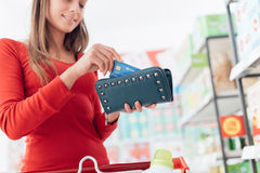Woman at the checkout. Woman at the supermarket checkout, she is taking a credit card from her wallet, shopping and retail concept Royalty Free Stock Photography