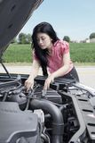 Woman checks a broken car Royalty Free Stock Photo