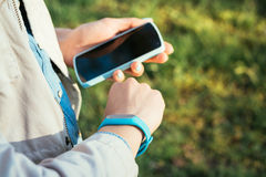 Woman checks data from fitness bracelet on a mobile phone Royalty Free Stock Image