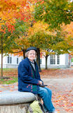 Woman checks email on campus in fall. A woman sits on a stone bench on a university campus in autumn. She is using a tablet computer Stock Photos