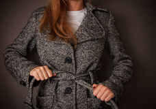Woman checks her coat Royalty Free Stock Photography