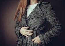 Woman checks her coat Royalty Free Stock Photo