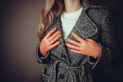 Woman checks her coat Royalty Free Stock Image