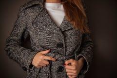 Woman checks her coat Stock Image