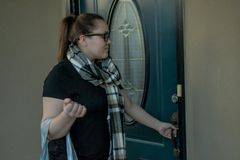 A woman locks her front door as she leaves home with a duffel bag over one arm. A woman checks her dark green front door as she leaves home with a baby blue royalty free stock images