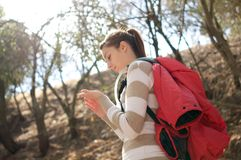 Woman checks her hand while hiking outdoors. On a sunny day Royalty Free Stock Photography