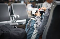 The woman checks her passport and plane ticket in the hand and waiting the plane in an international airport, Thailand royalty free stock images