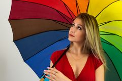 Woman with open umbrella looks up. Blonde person and wearing red Stock Photos