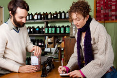 Woman checks off items from her shopping list Royalty Free Stock Images