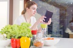 Woman checks the recipe Royalty Free Stock Photography