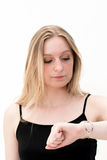 Woman checks time on her wrist watch Royalty Free Stock Images