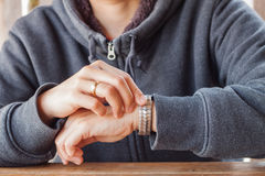 Woman checks the time on a wrist watch Stock Photography